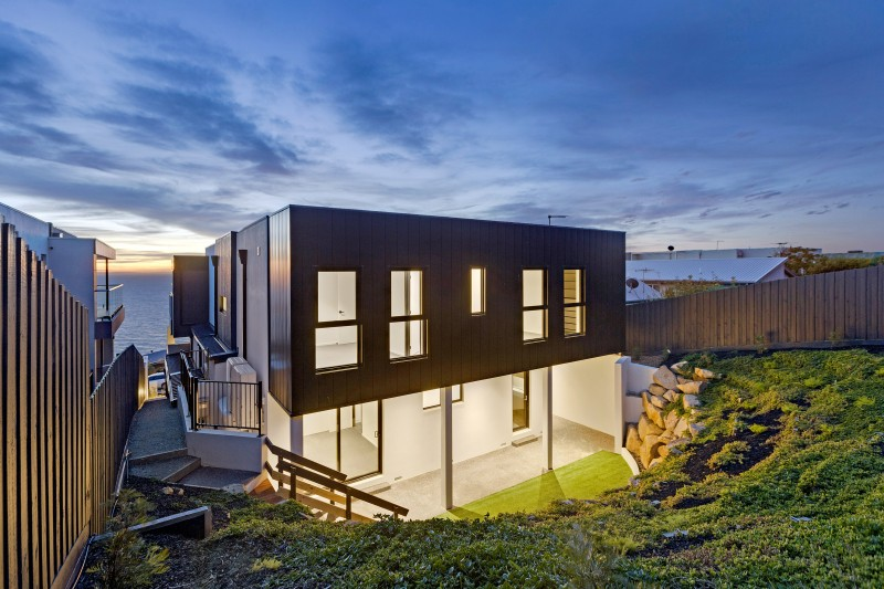 house on hillside by ocean